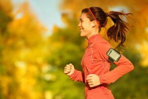 Woman runner running in fall autumn forest listening to music on smartphone using earphones. Female fitness girl jogging on path in amazing fall foliage landscape nature outside.